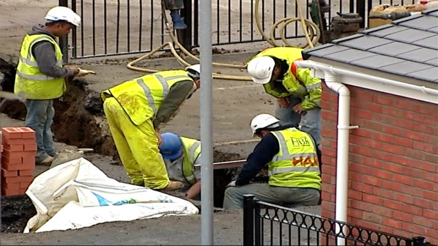 site construction delayed as travellers wait to be re-housed; england: london: newham: ext workmen in excavated hole in road surface pre-fabricated... - 長さ点の映像素材/bロール