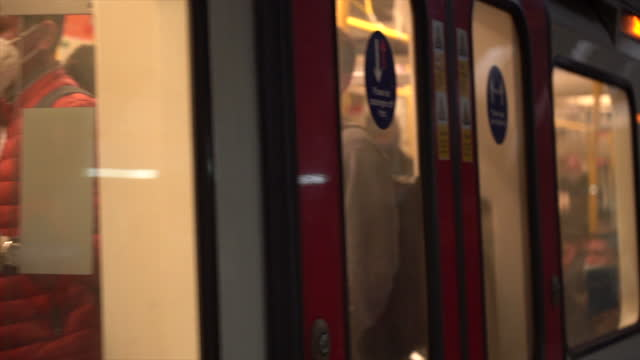 london 2021 underground trains arrive with masked commuters in carriage - underground station platform stock videos & royalty-free footage