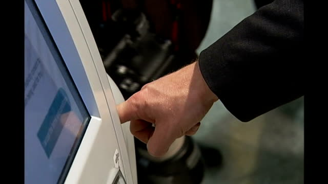 arrests update TX Heathrow Airport Liam Byrne MP placing his finger in biometric scanning machine Crowds in busy airport checkin area