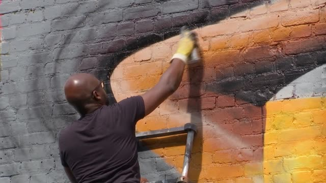 london artist dreph creates large murals across city england london shoreditch ext various of neequaye 'dreph' dsane with murals - itv london lunchtime news stock-videos und b-roll-filmmaterial