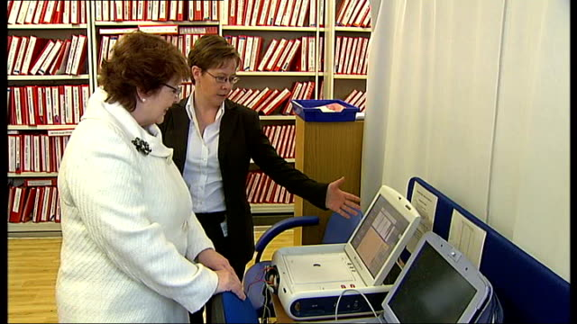 barts hospital: maureen sitting next to baroness thornton as showing her how remote heart monitoring device works computer screen showing information... - hand on heart stock videos & royalty-free footage
