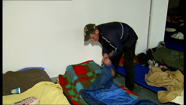 battersea: int various shots of andy frost entering temporary emergency homeless shelter and going to refreshment counter andy unfolding his sleeping... - homeless shelter stock videos & royalty-free footage