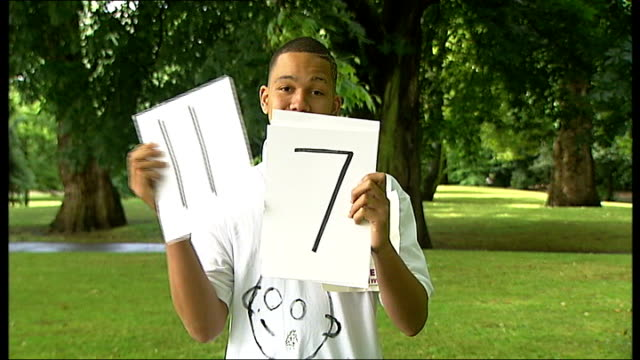battersea park: ext anthony bennett holding up numbered cards graphicised sequence anthony bennett, his best friend diyar barzenji, his girlfriend,... - battersea park stock videos & royalty-free footage