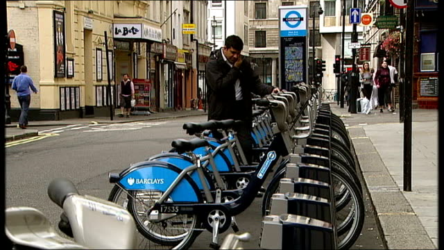 london bicycle hire scheme launched england london ext london bike hire scheme bicycles parked in docking bay area man riding bike hire bicycle along... - bicycle parking station stock videos and b-roll footage