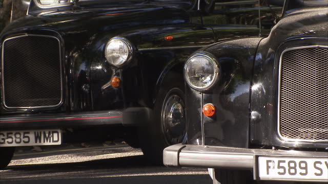 London black cab waits at crossing Available in HD.