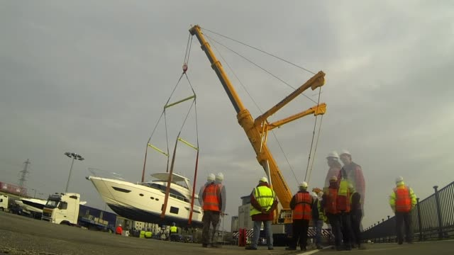 preparations england london ext boat along river luxury boats at dock lapse footage of boat being lifted out of river by crane and lowered onto... - london boat show stock videos and b-roll footage