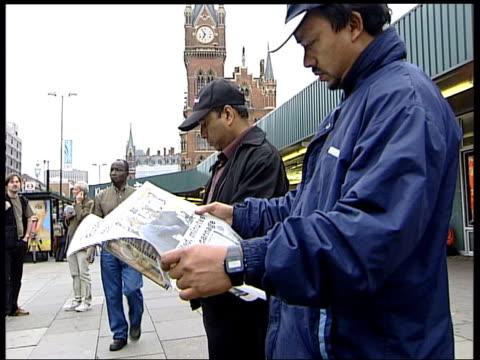 london bomb blasts aftermath: commuters at king's cross station; man reading 'metro' newspaper - bombardamento video stock e b–roll
