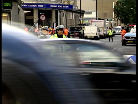 vidéos et rushes de aftermath two victims are named tx edgware road police officers stood at road block outside edgware tube station as traffic drives by ls underground... - salopette