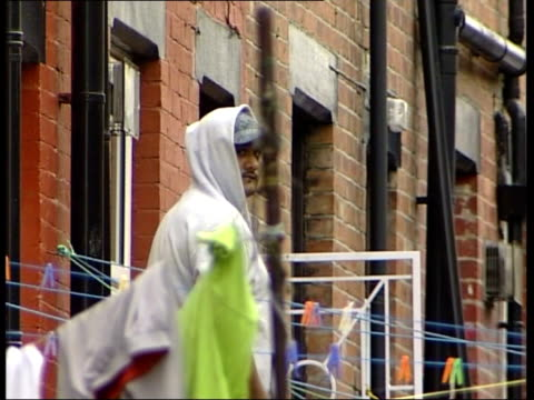 alleged bombers hasib hussain and mohammad sidique khan background leeds beeston la man and woman along litter strewn street lms man in baseball cap... - end cap stock videos & royalty-free footage