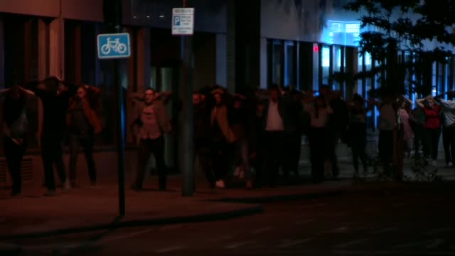 seven killed and 48 injured ext large group of people walking along road with their hands on their heads woman along road with others and crying... - london bridge england stock videos & royalty-free footage