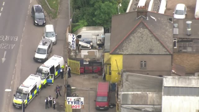 vídeos de stock, filmes e b-roll de two attackers named by scotland yard london dagenham view / aerial police vans and officers outside tyre depot raided in connection with the attack - tyre