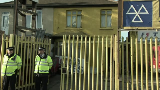 vídeos de stock, filmes e b-roll de two attackers named by scotland yard police officers guarding gates of tyre depot door of building smashed in by the police during raid vox pops sot - tyre
