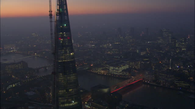 vidéos et rushes de london bridge over river thames glows red near the shard on a smoggy night. - aube