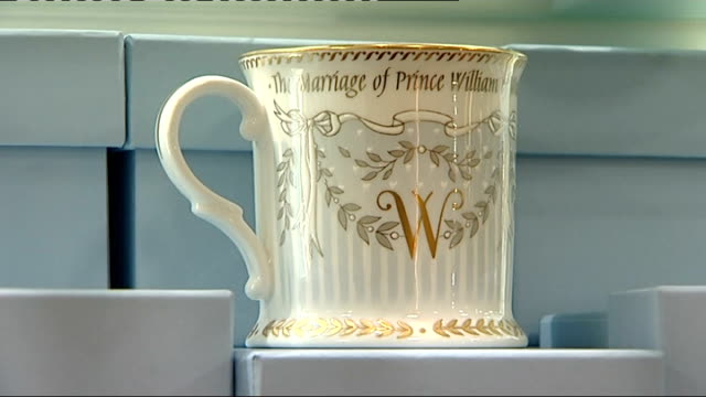 London Buckingham Palace gift shop INT Official royal wedding china on display in Buckingham Palace gift shop Man looking at china Commemorative pill...