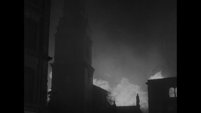 vs london buildings burning / firemen spraying water on fire with fire hoses / fireman silhouetted against fire climbing ladder to upper story of... - seconda guerra mondiale video stock e b–roll