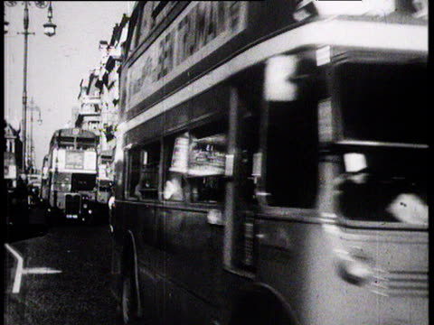 london buses and traffic along crowded oxford street london; 1957 - doppeldeckerbus stock-videos und b-roll-filmmaterial