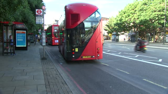 london buses general views; england: london: angel: ext passengers wearing face masks waiting at bus stop / passengers alighting and boarding buses - waiting stock videos & royalty-free footage