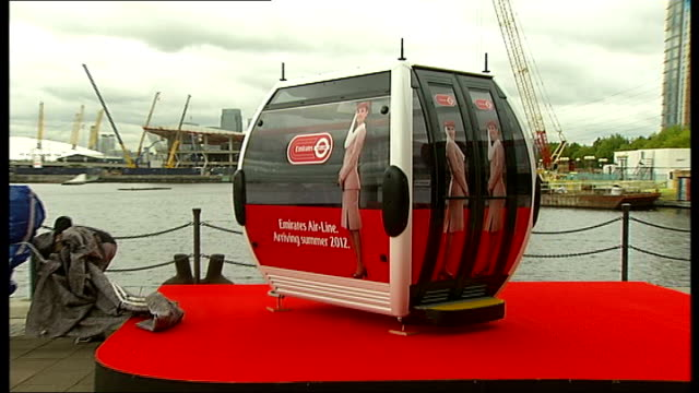 London cable car project unveiled ENGLAND London EXT Men removing tarpaulin from the model of a cable car gondola similar to those that will be...
