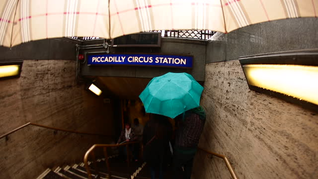 vidéos et rushes de london pov carrying umbrella looking up at underground sign and walking down steps into piccadilly circus station. - panneau d'entrée