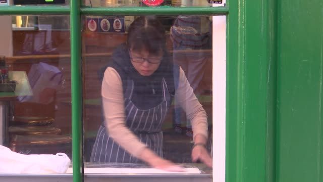 london soho chinatown ext various of woman rolling dough in window of chinese restaurant / gvs chinese restaurants / man preparing food at chinese... - gate stock videos & royalty-free footage