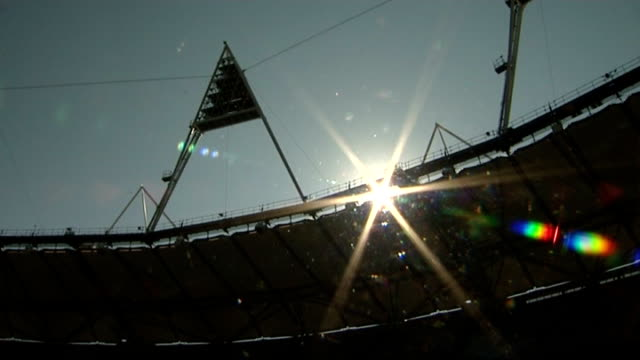 london chosen to host 2017 world athletics championships; roof and floodlights of olympic stadium silhouetted against sun - sun roof stock videos & royalty-free footage