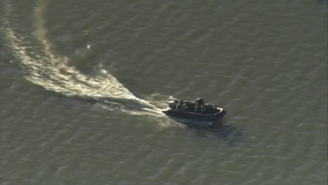 london city airport closed after unexploded bomb found in the thames; air view royal navy divers along river on dinghy - british military stock-videos und b-roll-filmmaterial