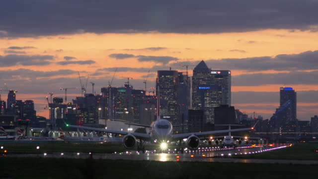 london city airport with canary wharf in the distance - taxiing stock videos & royalty-free footage