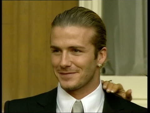 stockvideo's en b-roll-footage met london cms david beckham smiling at time of receiving his obe as v/o max clifford publicist phono interview sot if she was going to leave him in... - publiciteitsmedewerker