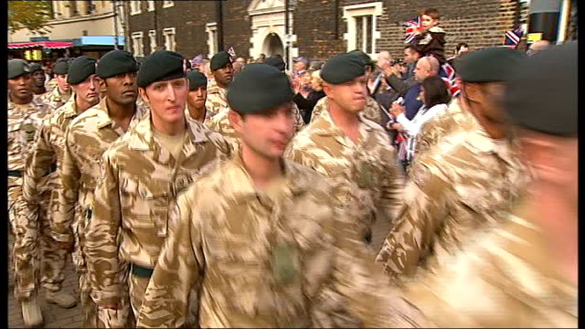 vidéos et rushes de croydon: ext **military band music heard sot** soldiers of 2nd battalion, the rifles parading along street people cheering and waving union jack... - infanterie