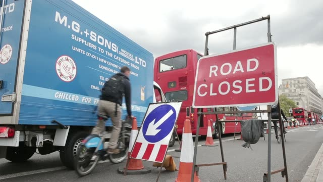 london double decker bus and a commercial van drive past a roadworks sign in a traffic jam on waterloo bridge in london, uk on thursday, april 24... - road closed englisches verkehrsschild stock-videos und b-roll-filmmaterial