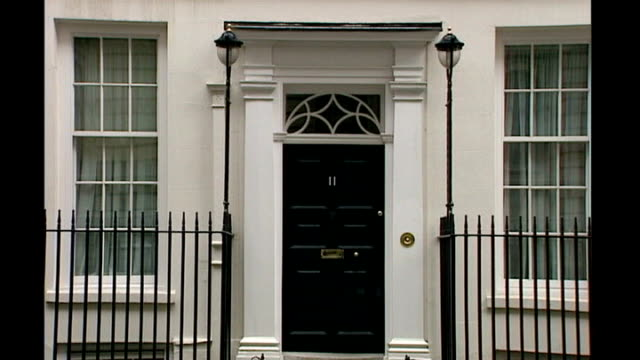 london downing street sequence of door to number 11 downing street residence of the chancellor of the exchequer as sound effects of gunfight overlaid... - chancellor of the exchequer stock videos and b-roll footage