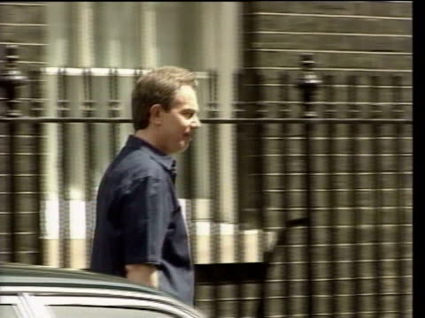 london downing street ext lms tony blair mp wearing jeans short sleeved shirt carrying red ministerial case out of number 10 zoom in pan ms blair... - jeans stock videos & royalty-free footage