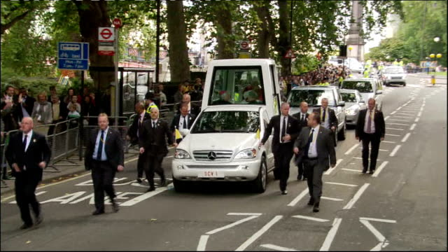 embankment: ext pope benedict xvi, in popemobile, waving as travelling slowly along past crowds - ローマ法王専用車点の映像素材/bロール