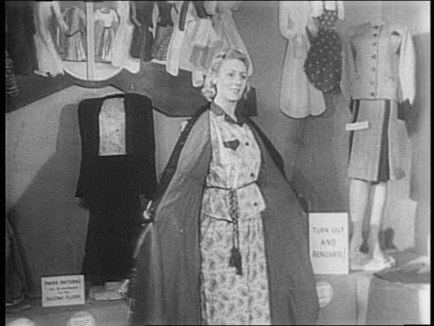 london, england / building with sign above entrance 'the wartime layette' / layette workers show mothers how to make a bassinet out of chairs and... - 1943 stock-videos und b-roll-filmmaterial