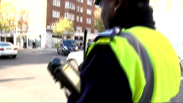London EXT Driver discussing unfairness of ticket with traffic warden SOT Traffic warden along main road Close shot of traffic warden preparing...
