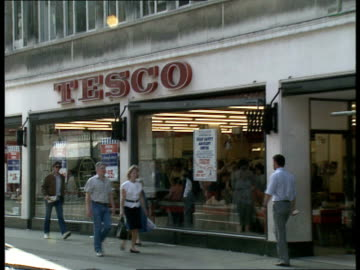 """stockvideo's en b-roll-footage met london: ext gv's of tesco supermarket with poster in window saying """"this store is supporting the food safety advisory centre"""", people shopping inside... - shopping centre"""