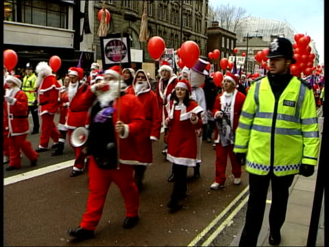 london fathers 4 justice protestors in santa claus outfits carrying placards reading 'put the father back into christmas' along la protestor walking... - stilts stock videos and b-roll footage