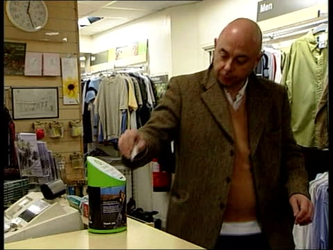 london ext oxfam charity shop oxfam sign 'earthqauke tsunami any change will definitely help' man placing â£10 note in donation box cs pound coin... - donation box stock videos & royalty-free footage