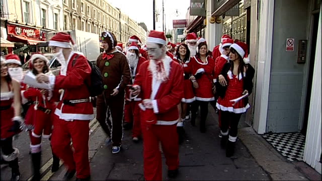 london ext people dressed as father christmas along as taking part in santacon event back view people in santa outfits santacon participants walking... - lager stock videos & royalty-free footage
