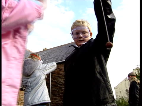 london ext primary school children in playground wearing goggles as play conkers clean feed tape = d0509191 or programme as broadcast tape = d0509190 - skibrille stock-videos und b-roll-filmmaterial