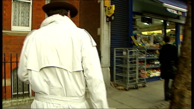 vidéos et rushes de london ext reconstruction of back view of reporter along gray's inn road and into 'andrew's cafe' as followed by 'private detective' in white mac... - mac