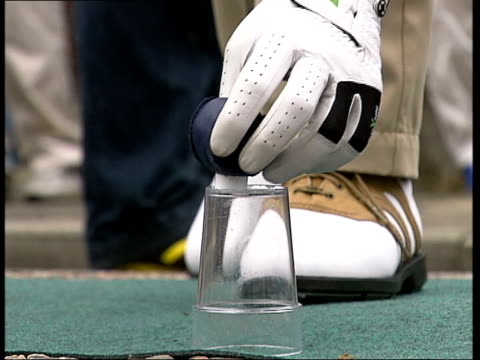 london ronan rafferty teeing off in street during 'urban golf' match leather golf ball placed onto upturned cup ball next hole golfer hitting ball... - minigolf stock-videos und b-roll-filmmaterial