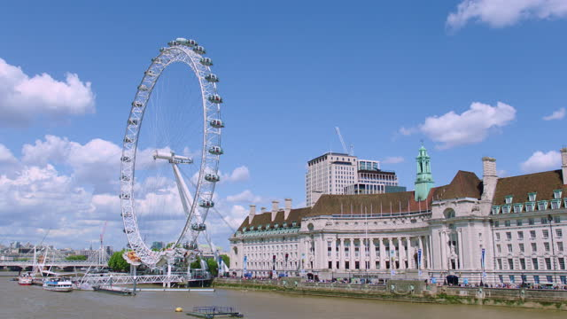 london eye (millennium wheel) and buildings of south bank beside the river thames / london, england - general view stock videos & royalty-free footage