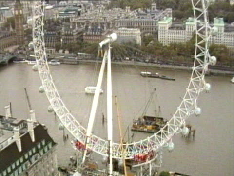 london eye as wheel rotates and pods are attached river traffic behind; oct 99 - erezione video stock e b–roll