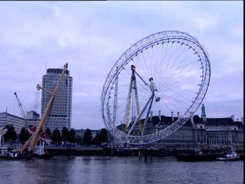 london eye at angle during lift to vertical; 07 oct 99 - millennium wheel stock videos and b-roll footage