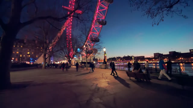 london eye observation wheel and tourists at night on london's southbank. - tourist stock videos & royalty-free footage