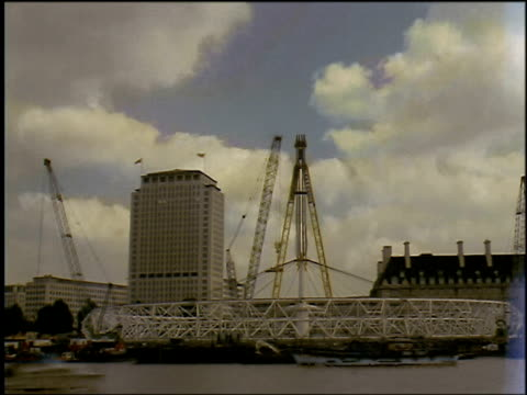 london eye whilst still horizontal over thames with cranes moving - erezione video stock e b–roll