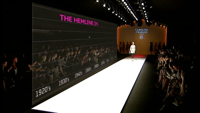 economic outlook models along catwalk at show by designer caroline charles as graphic illustrating the hemline index - london fashion week stock videos and b-roll footage
