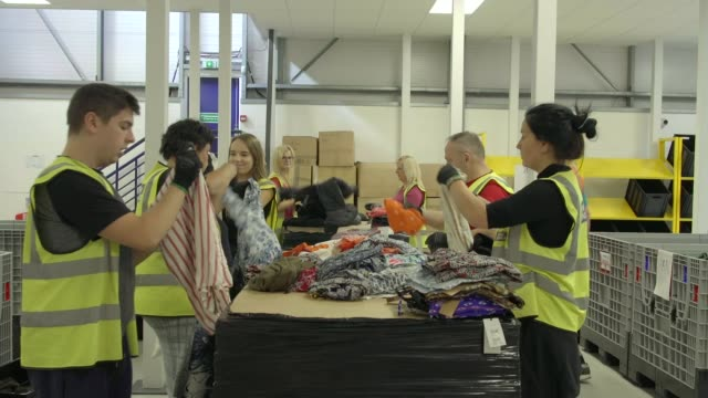 london fashion week ss20 / extinction rebellion: activists stage 'die in' protest; england: int various shots of workers folding clothes in fabric... - recycling stock-videos und b-roll-filmmaterial