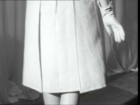london: mayfair: celanese house: light coat over dark dress ) by mattli bowler ) grecian evening dress: ) celanese house tilt up: ) tilt up tunic... - knitting needle stock videos & royalty-free footage